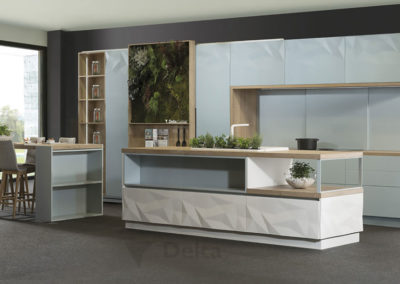 C11 Cocina exclusiva con puerta en relieve lacado combinado en tres colores, detalle de puerta corredera con jardín vertical y estantes. Isla partida  con cajones contenedores y  zona de desayunos.