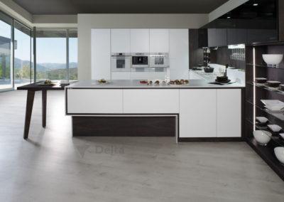 C2 Cocina con forma de U, en madera y estratificado, puerta con canto biselado a 45º, electrodomésticos en cristal blanco en columna, con detalle de mesa extraíble para economizar el espacio.