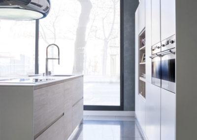 C6 Detalle de cocina compacta en material laminado en dos colores, con electrodomésticos integrados, tirador gola, interiores hidrófugos.
