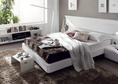 DM11 Dormitorio línea moderna lacado en blanco con original cabecero con forma de sobre con luz, mesillas largas de 1 cajón con bancada y sinfonier a juego.