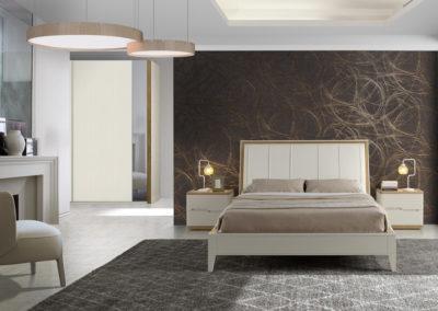 DM12 Dormitorio en chapa de madera en crema, combinado con detalles en color natural, bancada con patas, cabecero tapizado en piel, armario puertas correderas a juego con espejo.