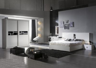DM3 Dormitorio de línea recta en blanco con detalles en cristal negro, con cómoda baja a juego, y armario de puertas correderas a medida.